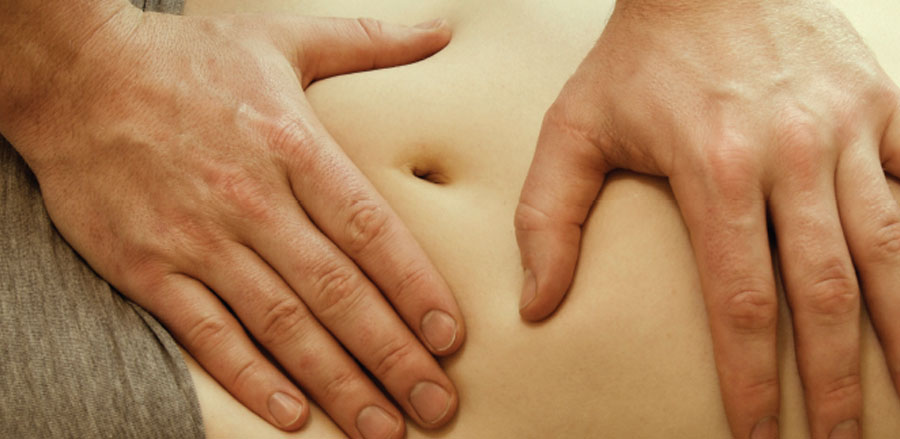 Physician palpating a patient's abdomen